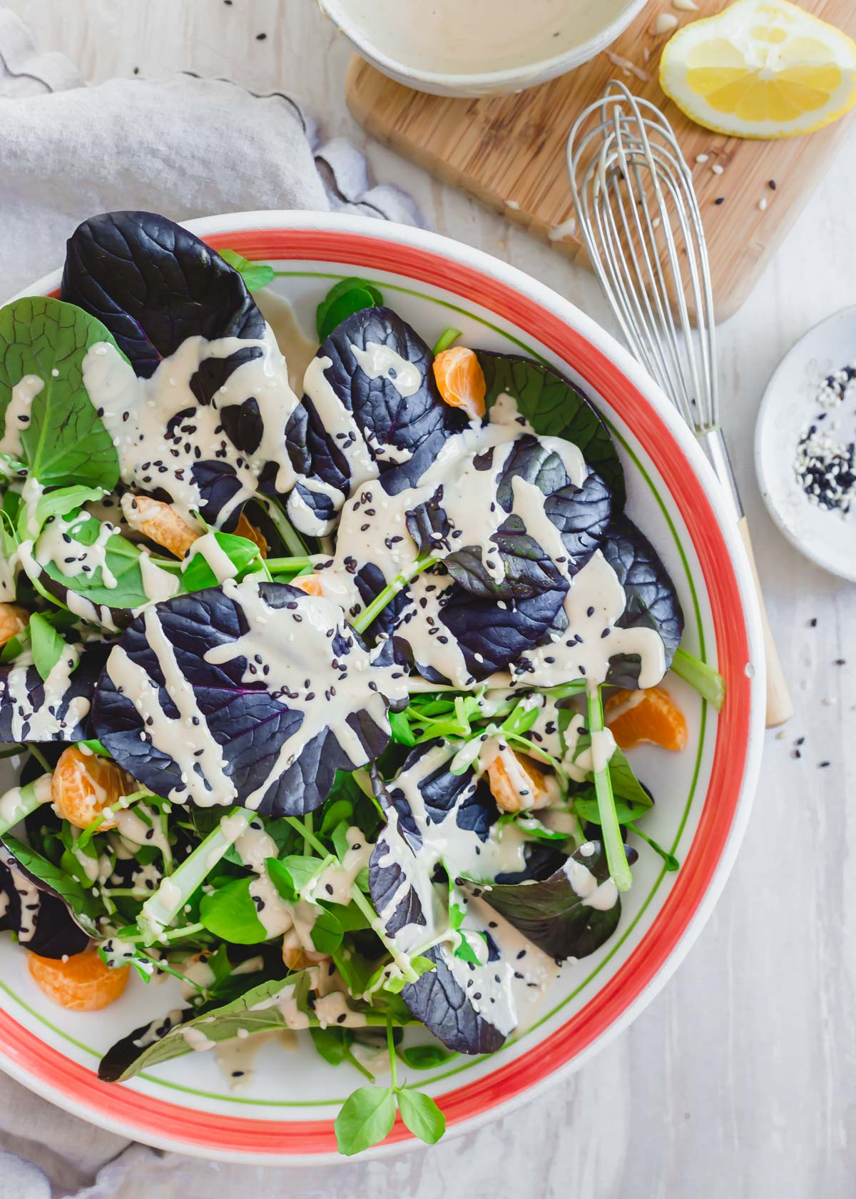 Purple tatsoi salad recipe in a bowl with pea shoots and clementines in a creamy tahini dressing.