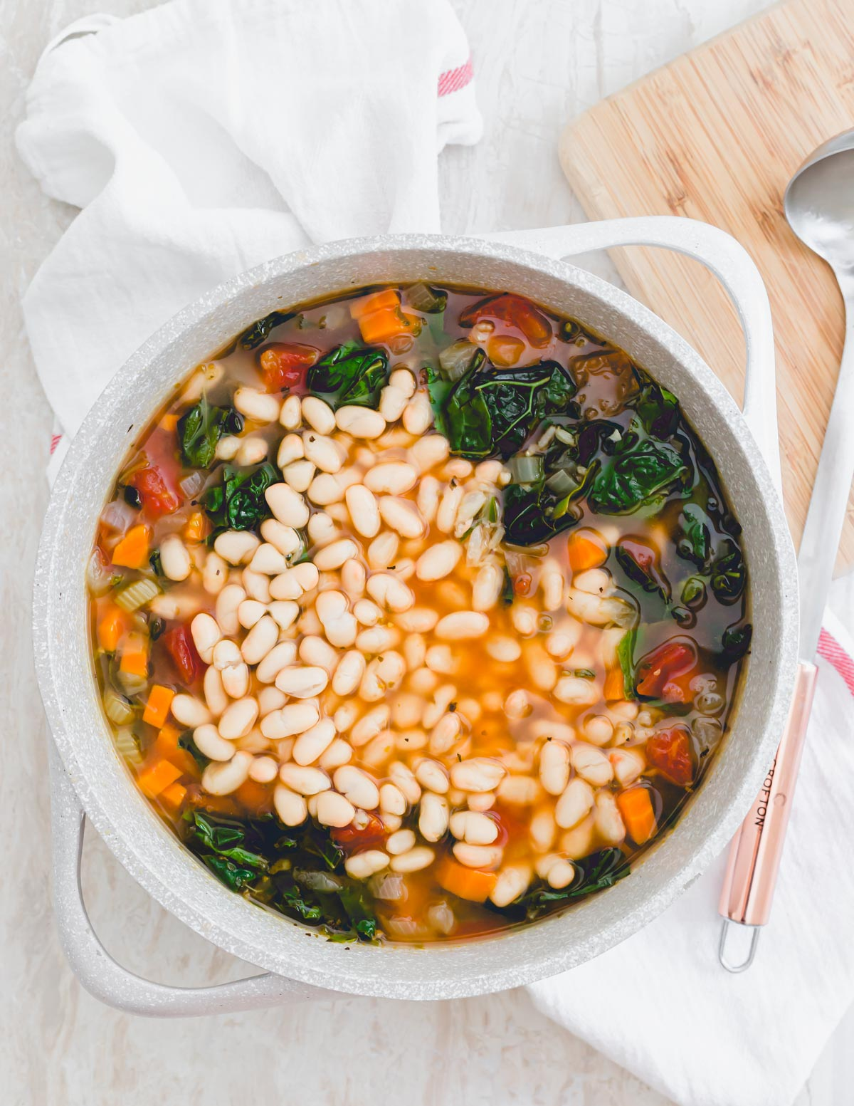 A pot of Tuscan kale soup with added white beans and ladle on the side.