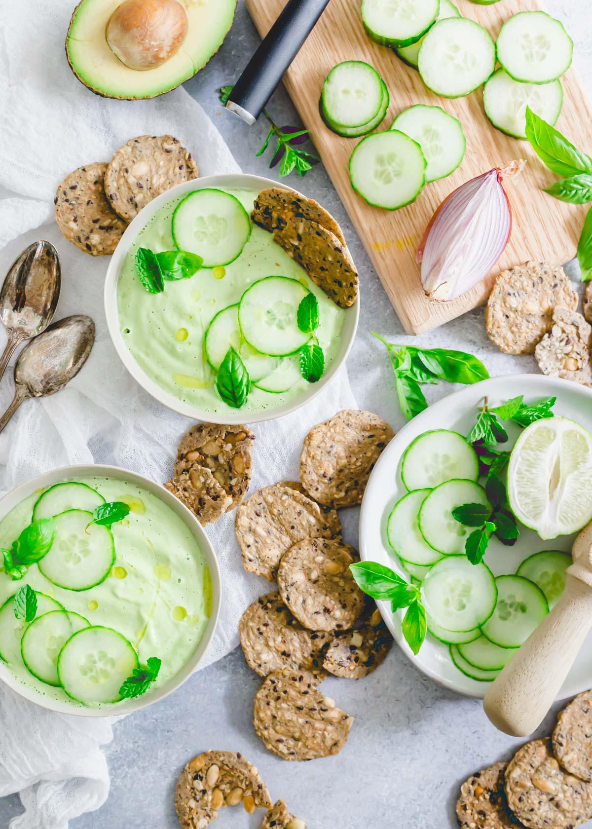 Raw cucumber gazpacho recipe served with gluten-free crackers and fresh herbs.