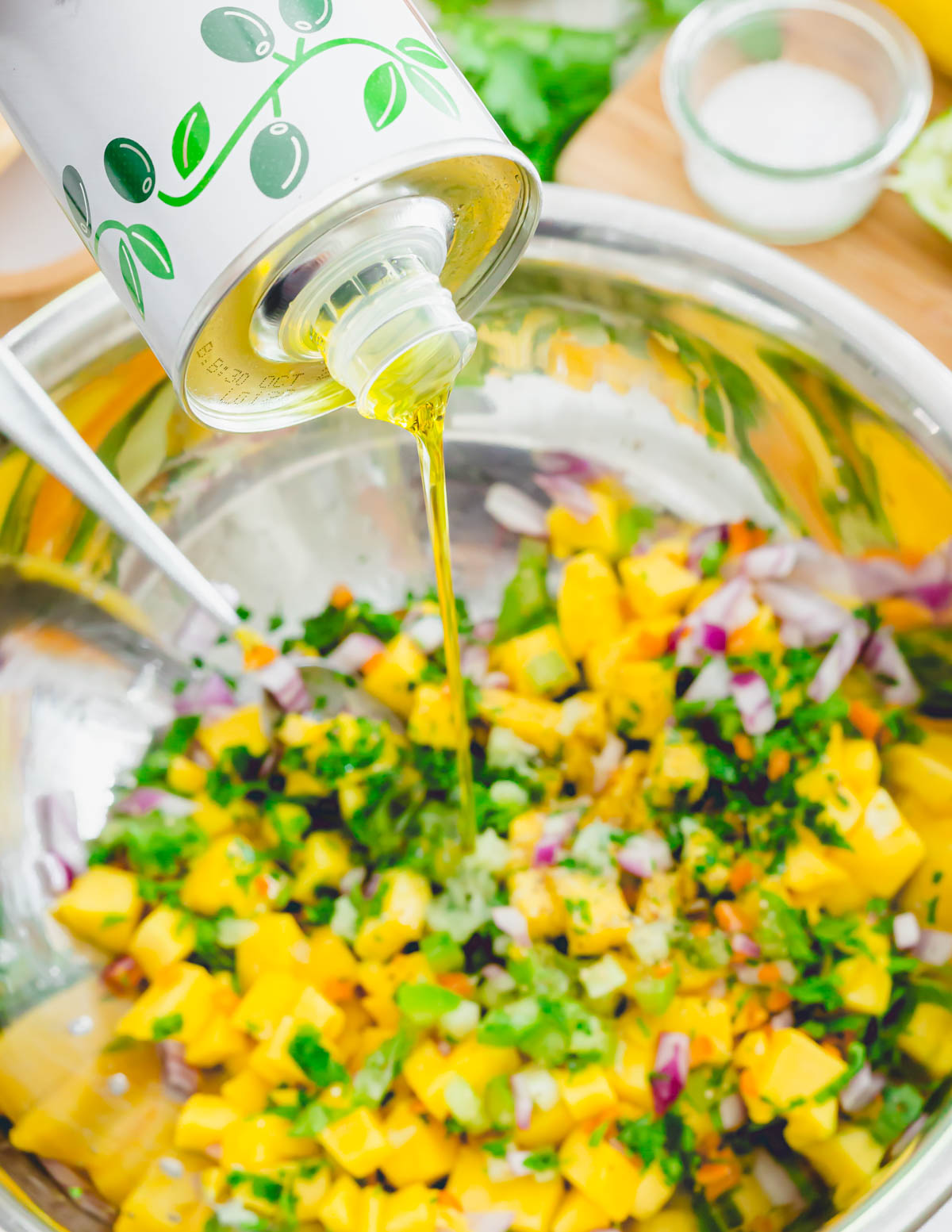 Pouring extra virgin olive oil into a bowl of mango habanero salsa.