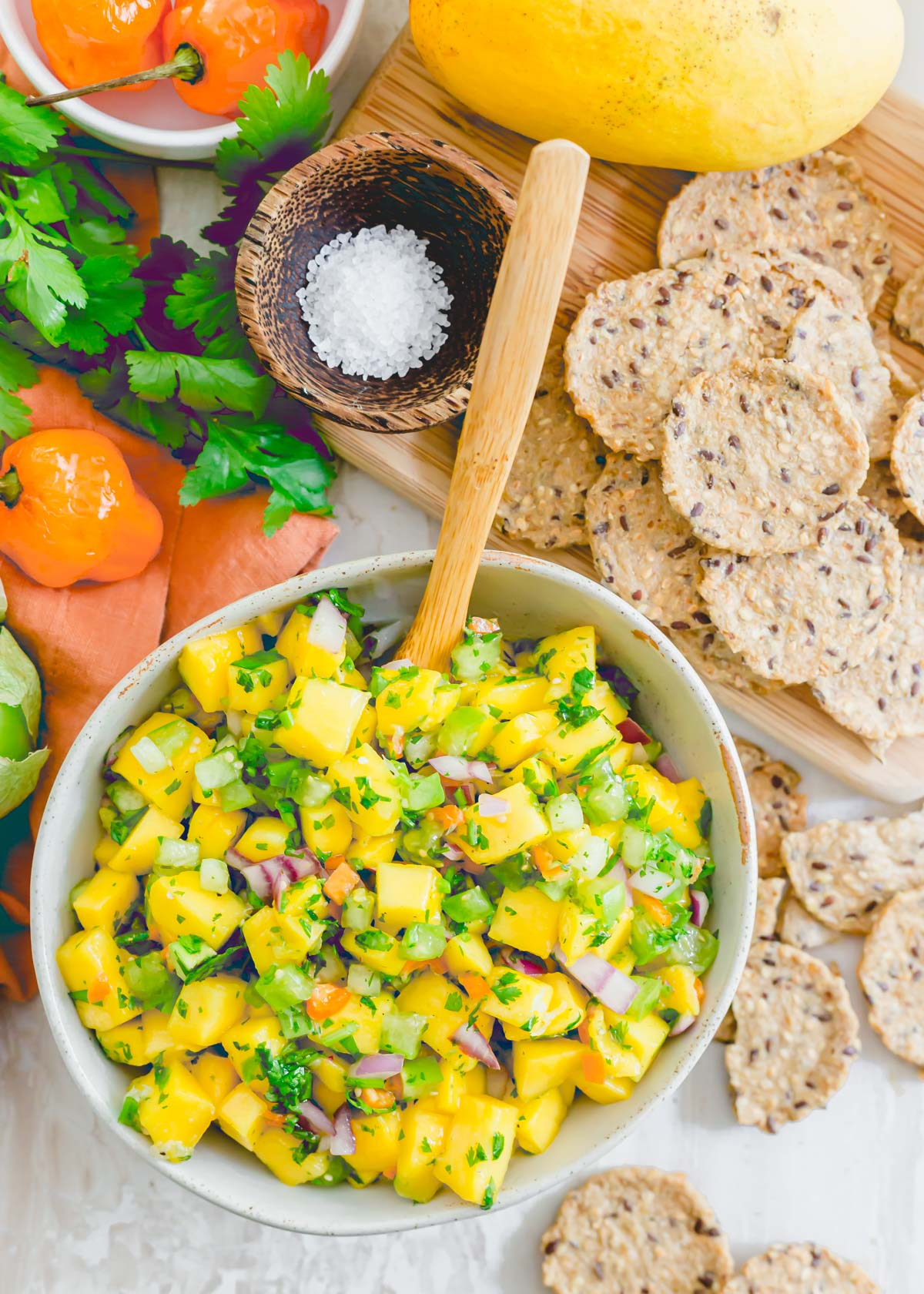 Fresh mango salsa with habanero peppers in a bowl with crackers on the side for serving.