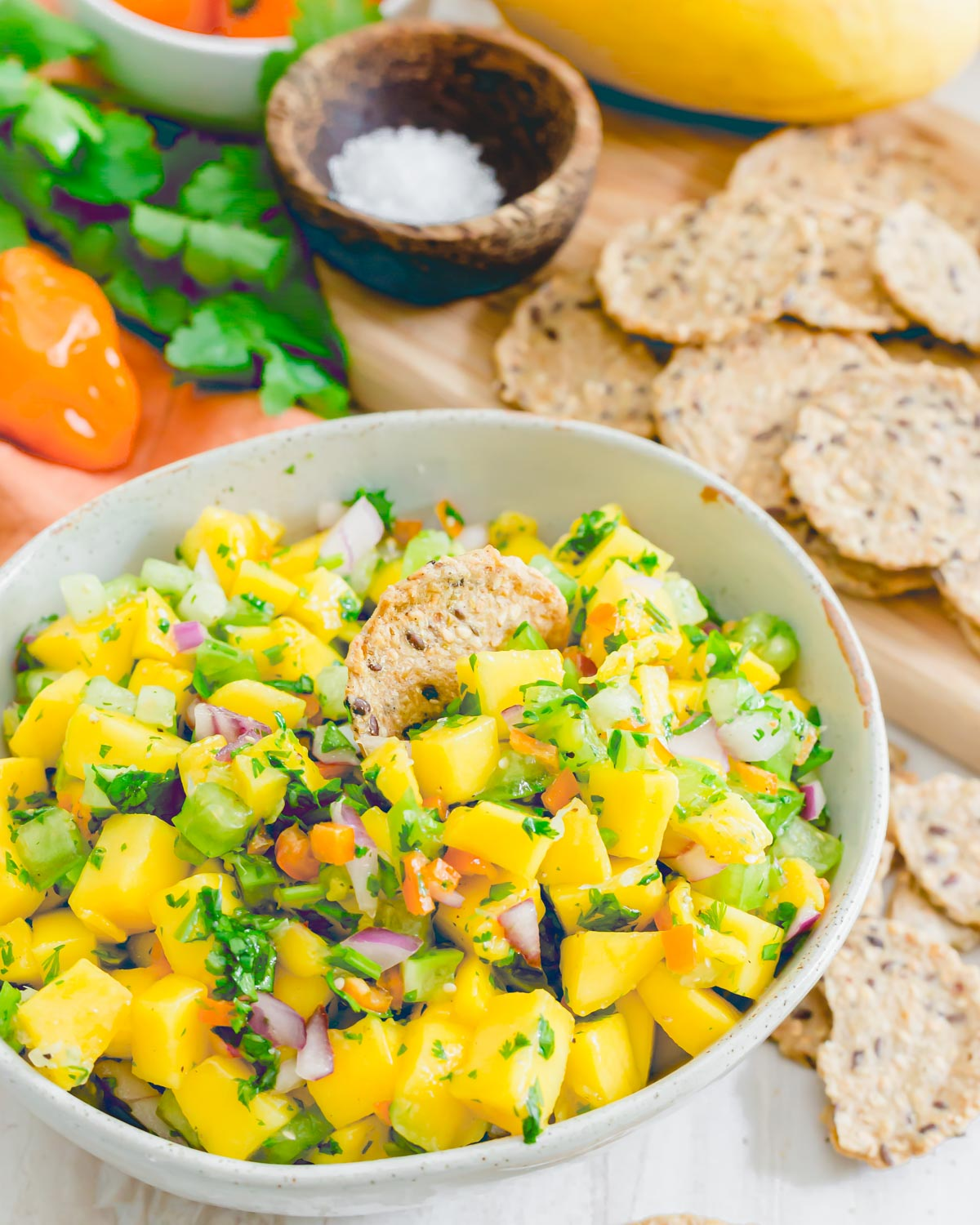 Cracker in a bowl of mango salsa with habanero peppers, cilantro, red onion, tomatillos and lime juice.