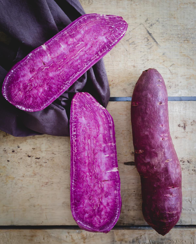 Stokes purple sweet potatoes, one whole, one cut in half on a wooden board.