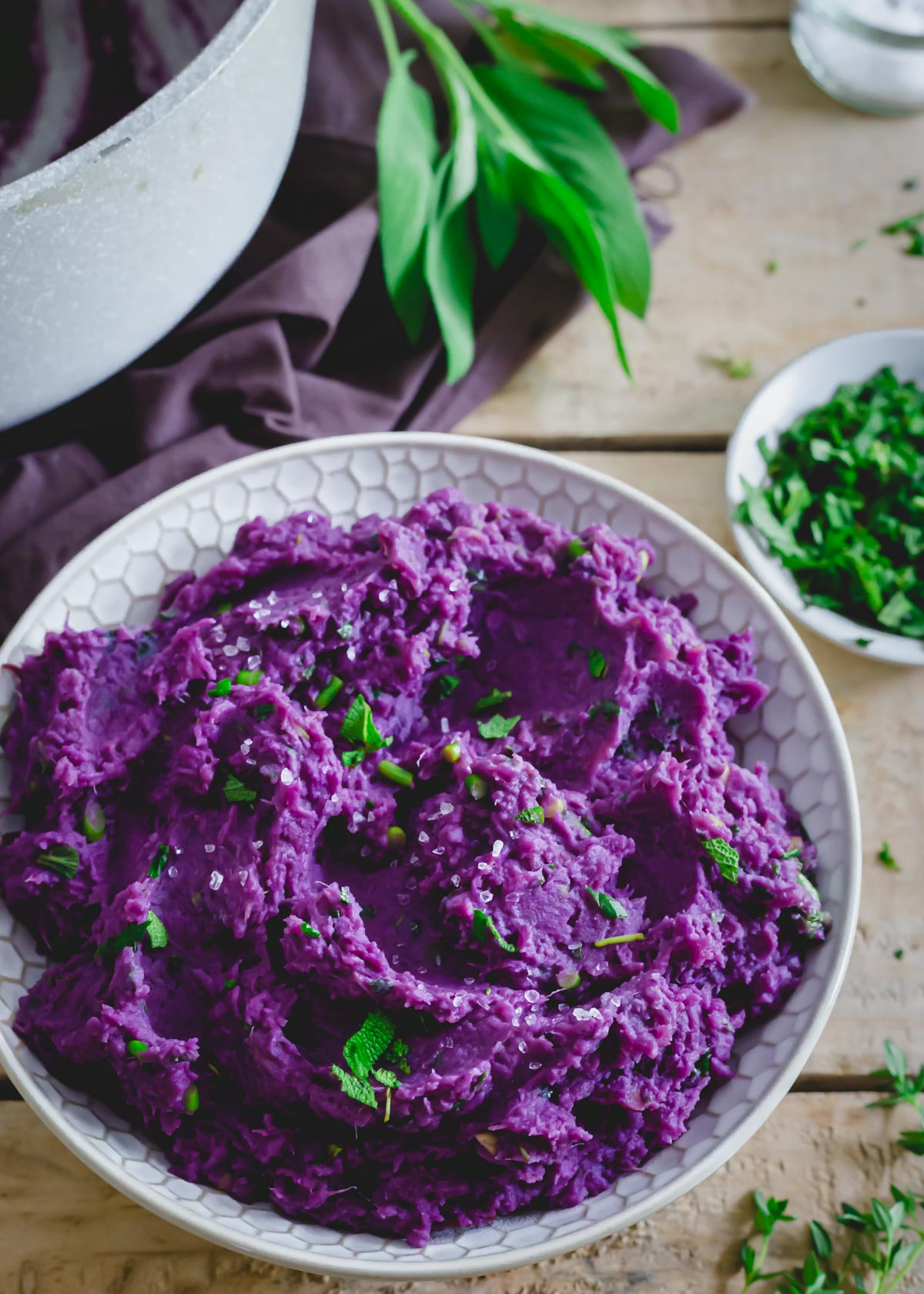 Creamy purple mashed sweet potatoes in a dish with herb butter sauce and sea salt.