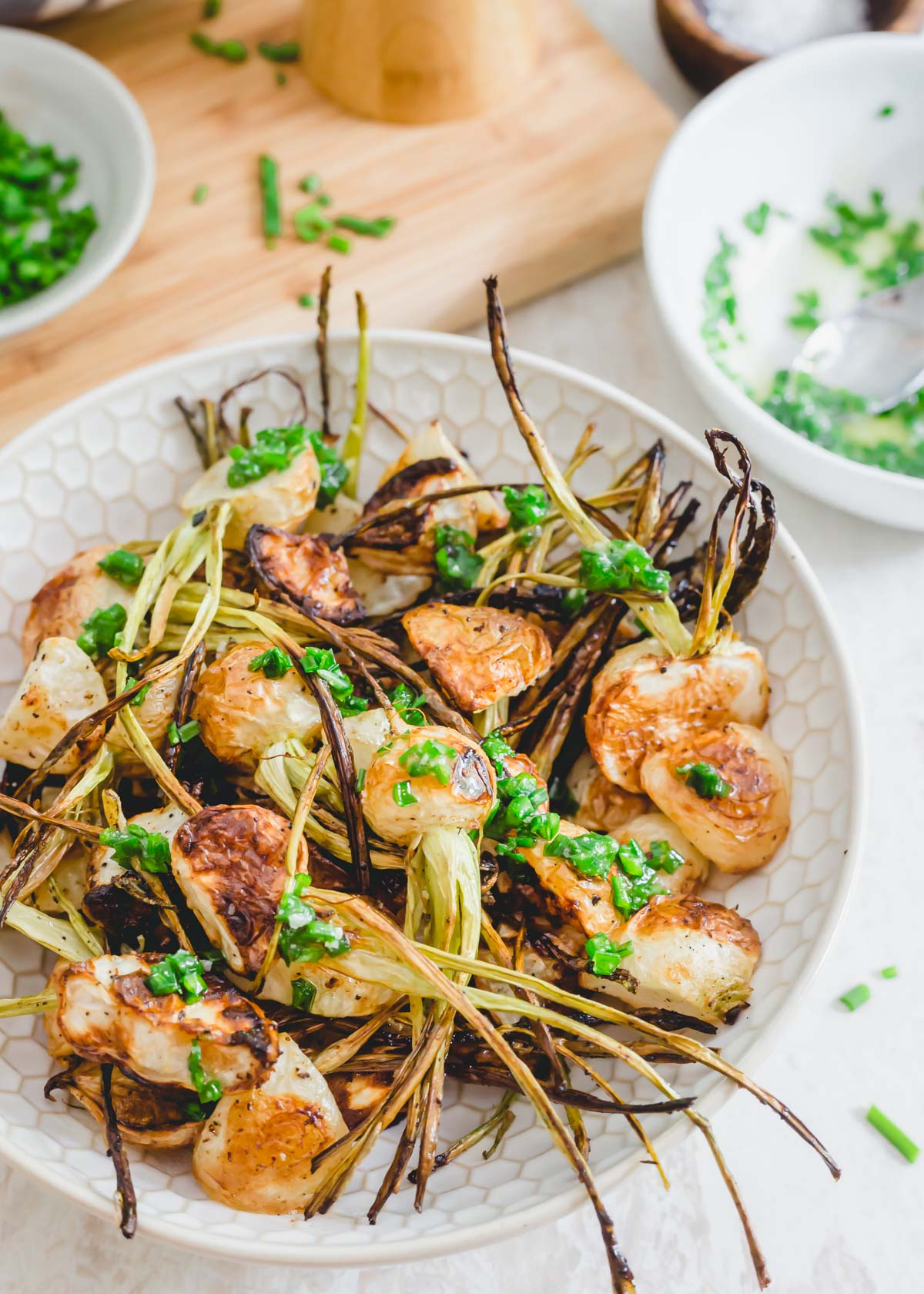 Crispy roasted white turnips with stems drizzled in a melted butter chive sauce.