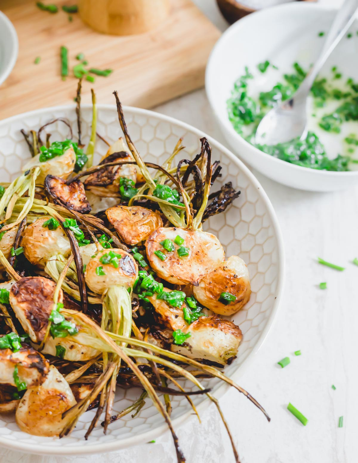 Crispy roasted turnips with stems attached in a bowl drizzled in a melted butter chive sauce.