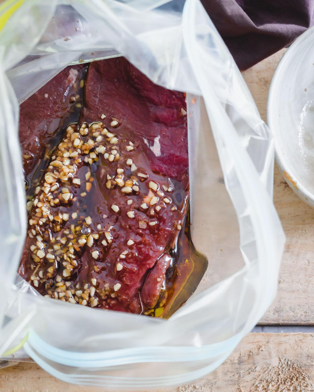 Venison backstrap marinating in a plastic bag overnight.