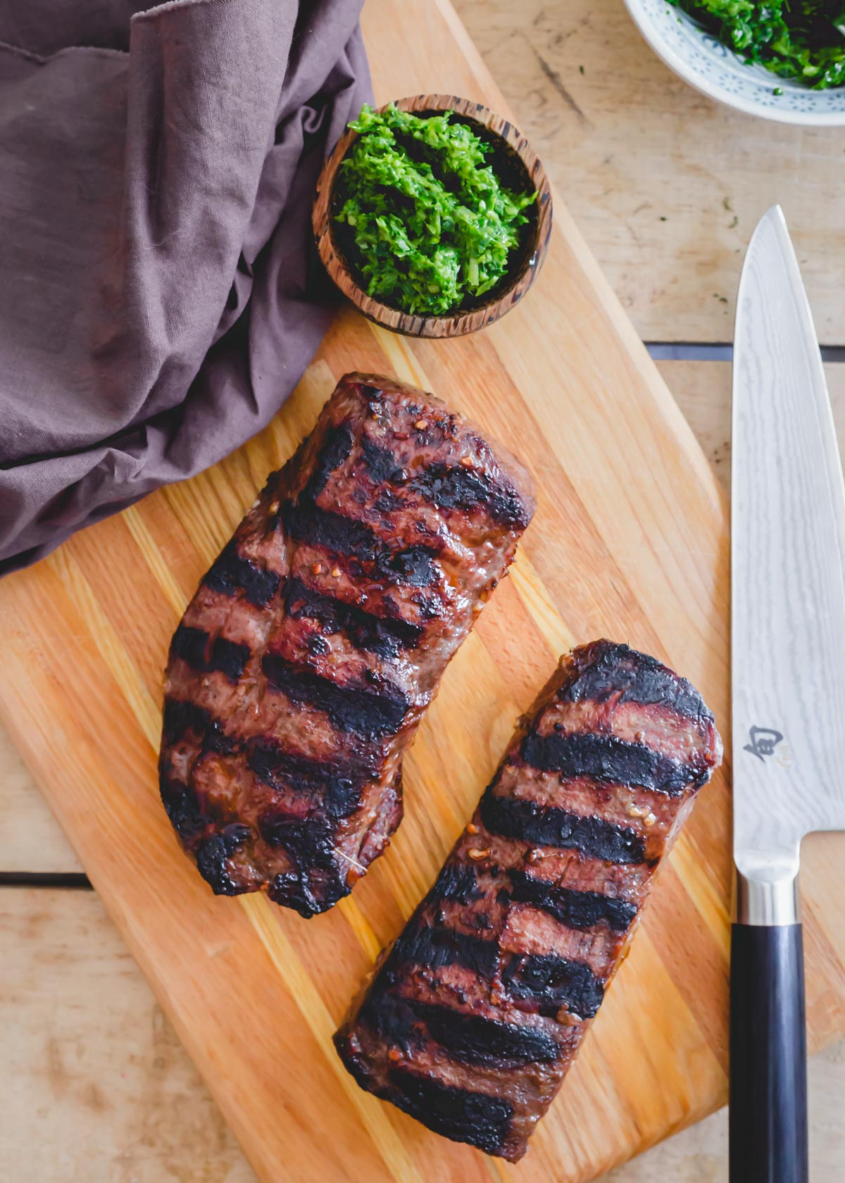 Two pieces of grilled venison backstrap on a cutting board.