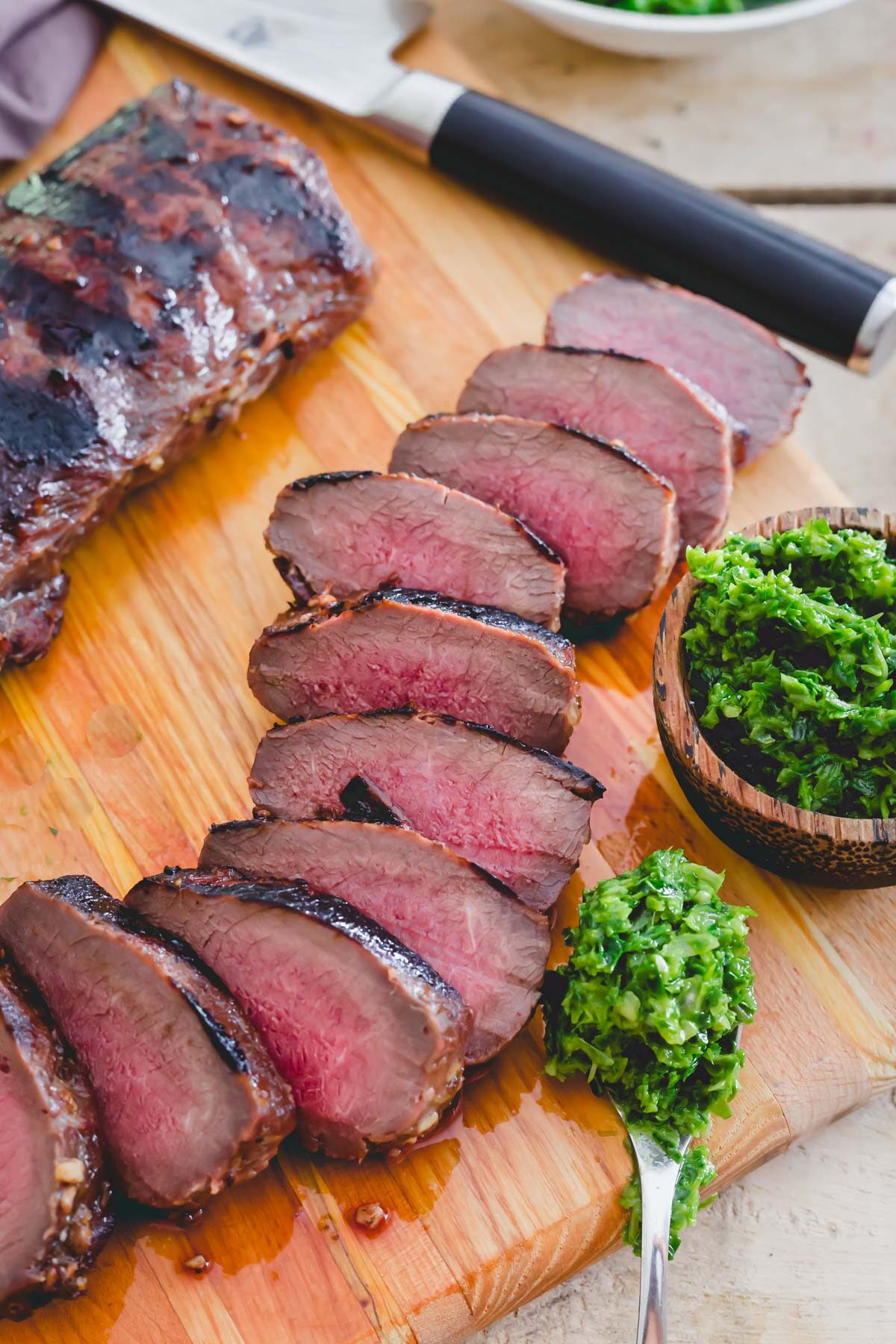 Venison backstrap recipe grilled and sliced on a cutting board with pesto on the side.