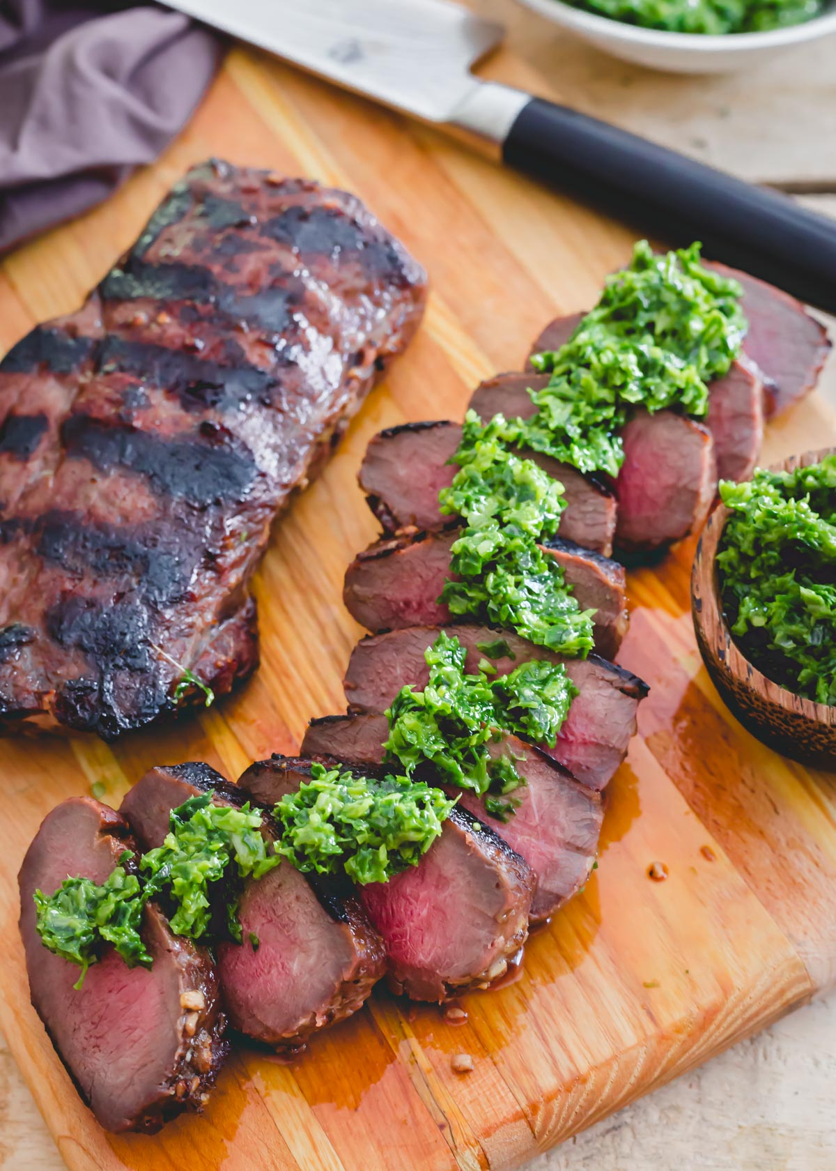Easy recipe for deer backstrap marinated, grilled and sliced on a cutting board with pesto.