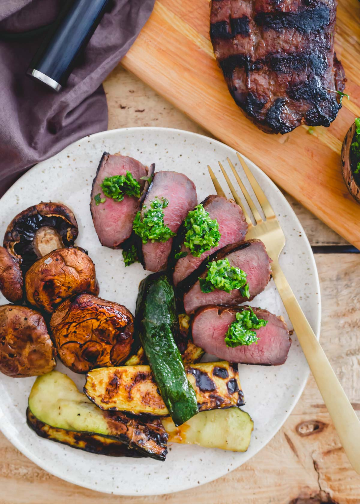 Grilled venison backstrap sliced on a plate with grilled vegetables on the side.