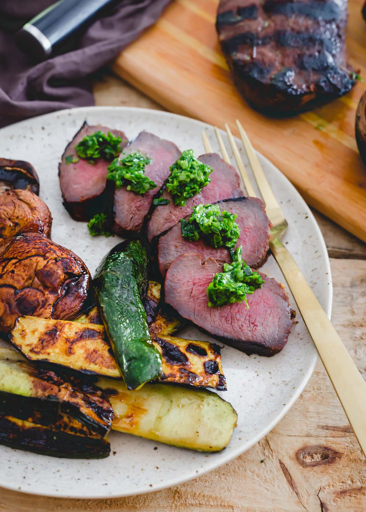 Medium rare grilled venison backstrap sliced and served with pesto and grilled vegetables on a plate.