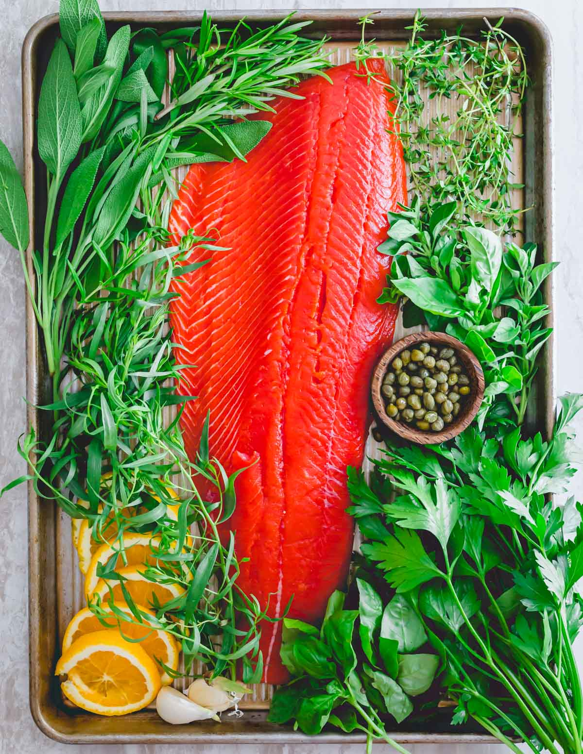 Raw wild sockeye salmon from Alaska with fresh herbs, garlic, capers and orange slices on a baking sheet.