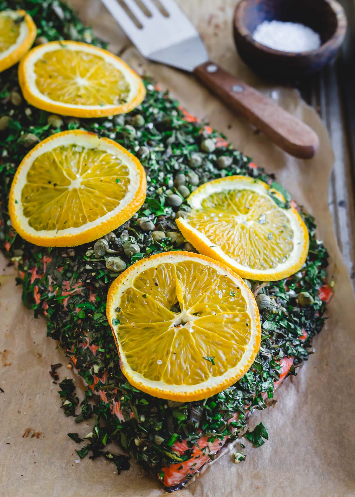 Baked sockeye salmon recipe with fresh herbs, garlic, capers and citrus.