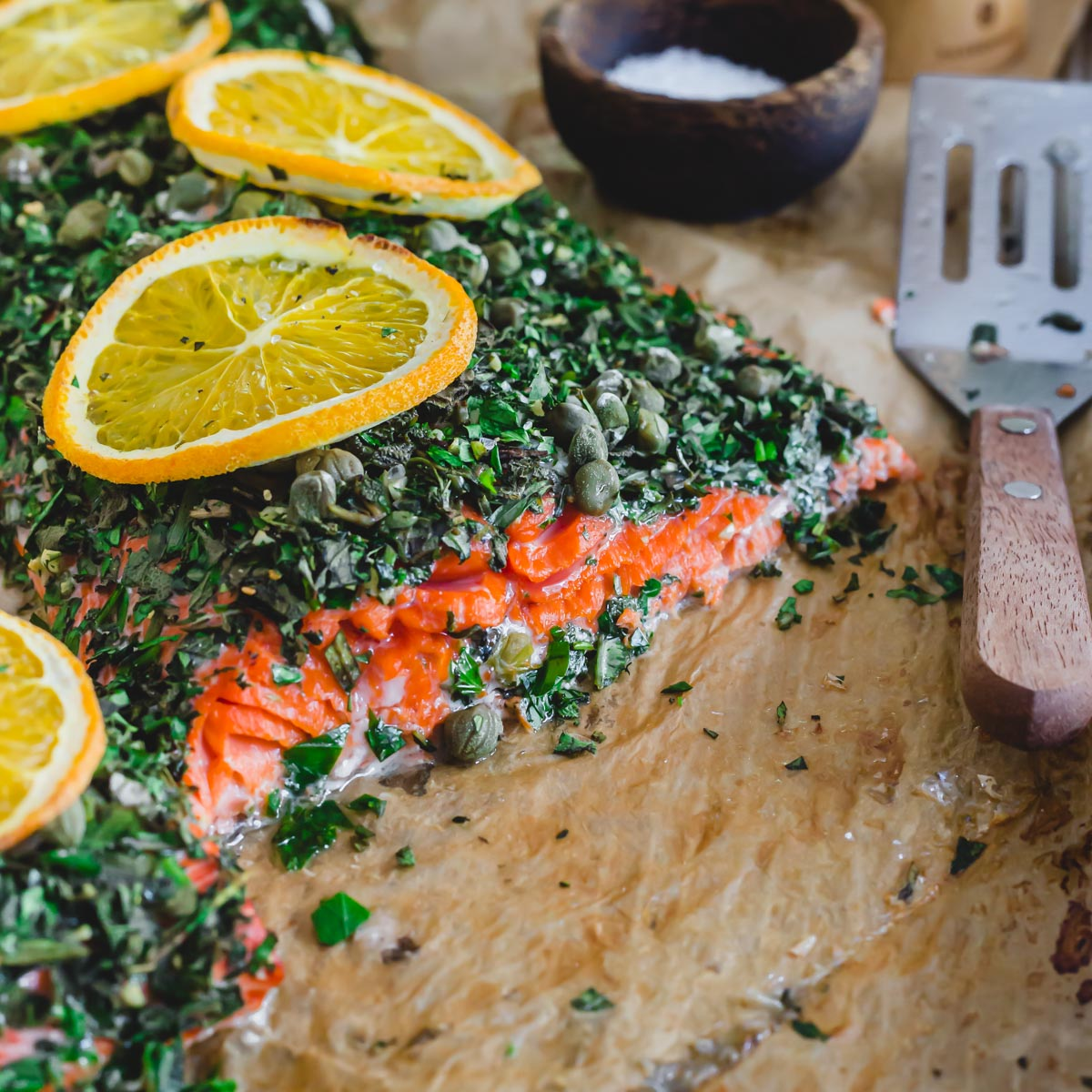 Bright red baked wild sockeye salmon with an herb crust on a baking sheet with spatula for serving.