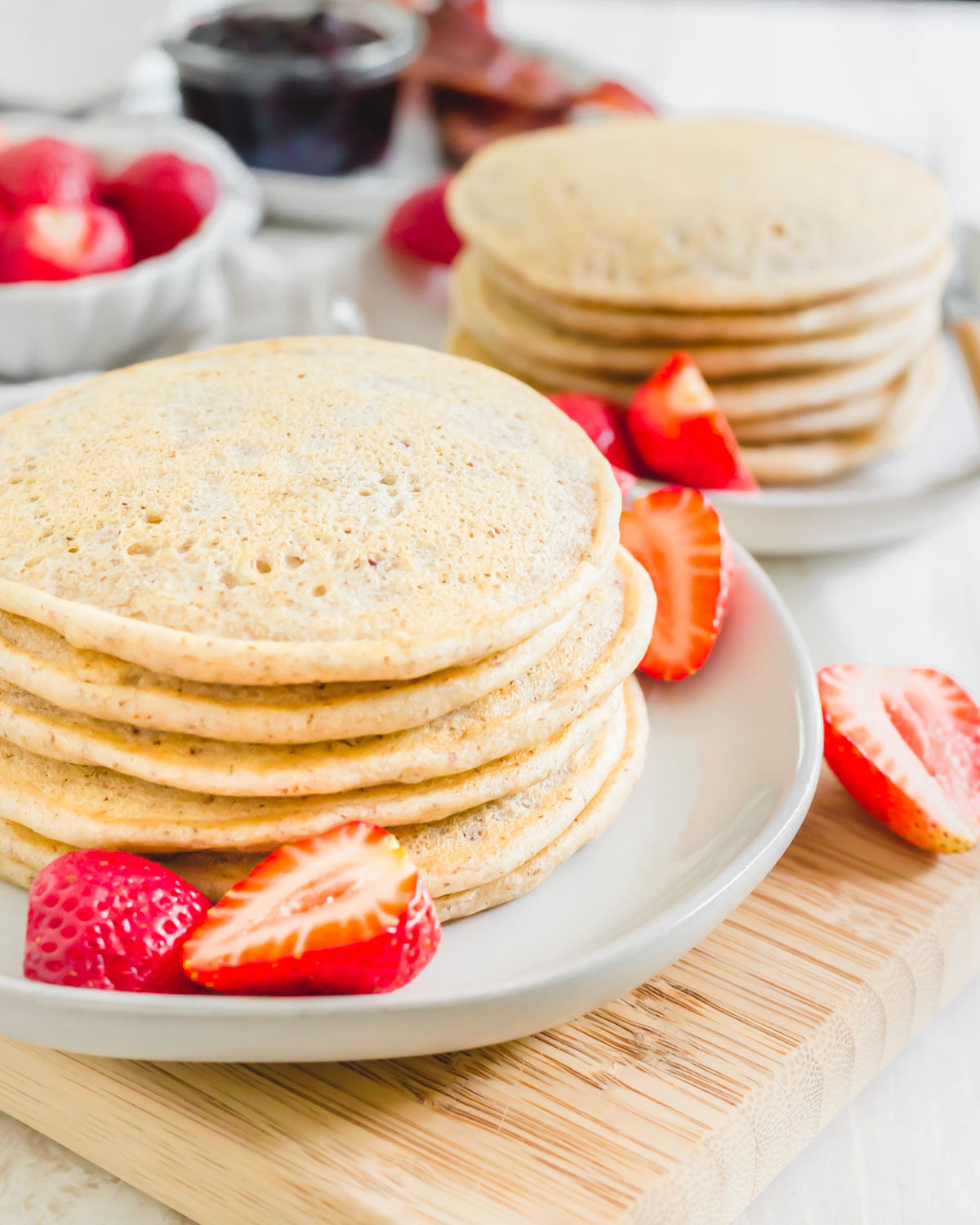 Cassava flour pancake stack with strawberries on a plate.