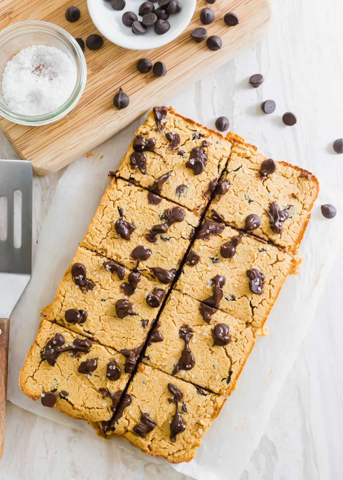 Baked chickpea blondies cut into 8 bars and sprinkled with flaky sea salt.
