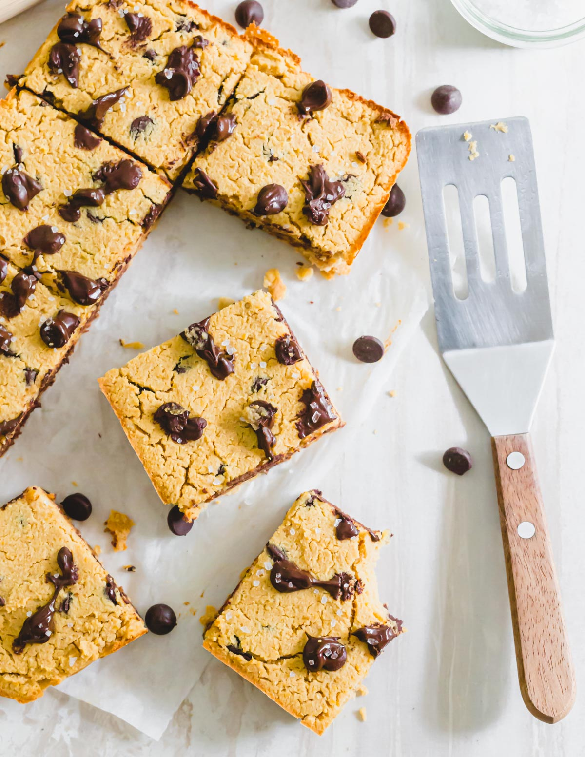 Naturally vegan and gluten-free chickpea blondie recipe with chocolate chips cut into bars and garnished with coarse sea salt.