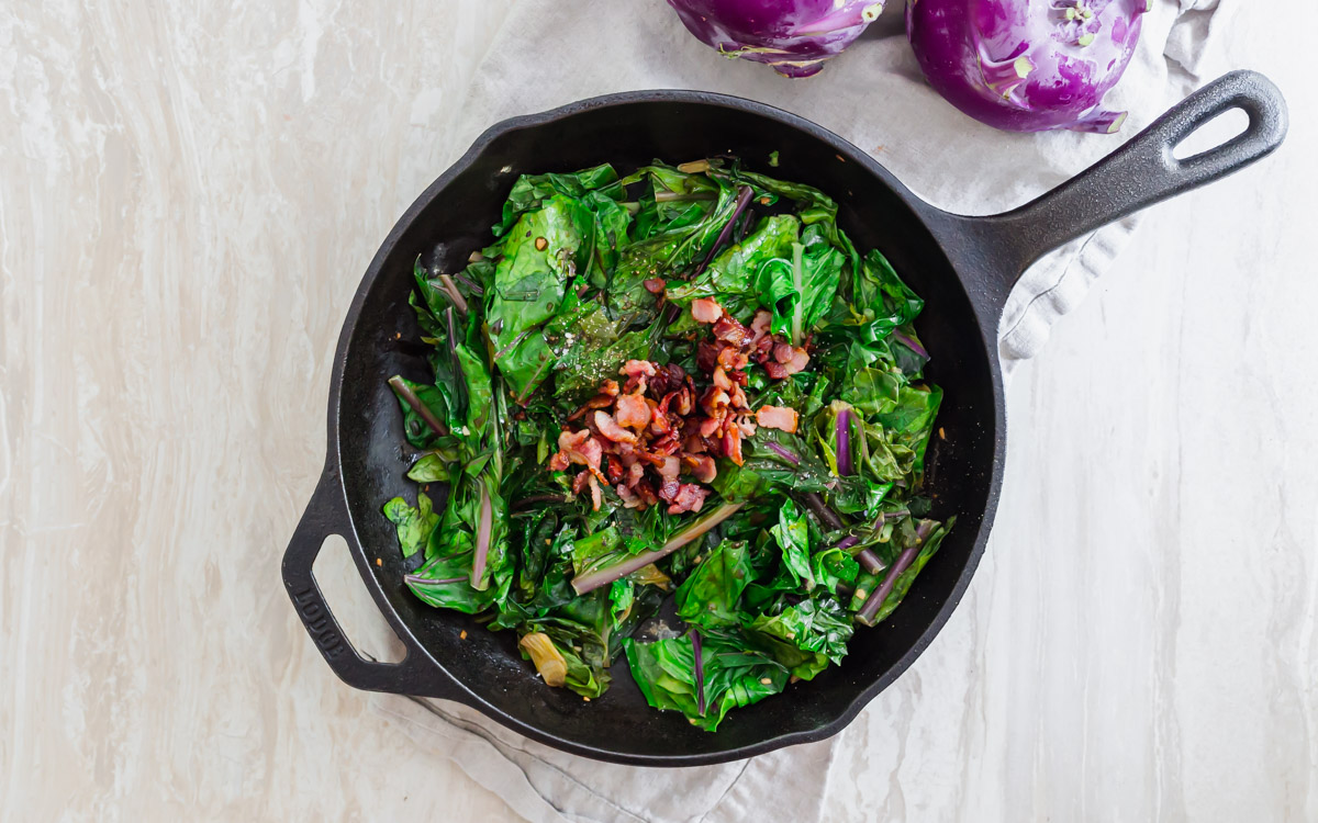 Bacon topped cooked kohlrabi greens with garlic and scallions.