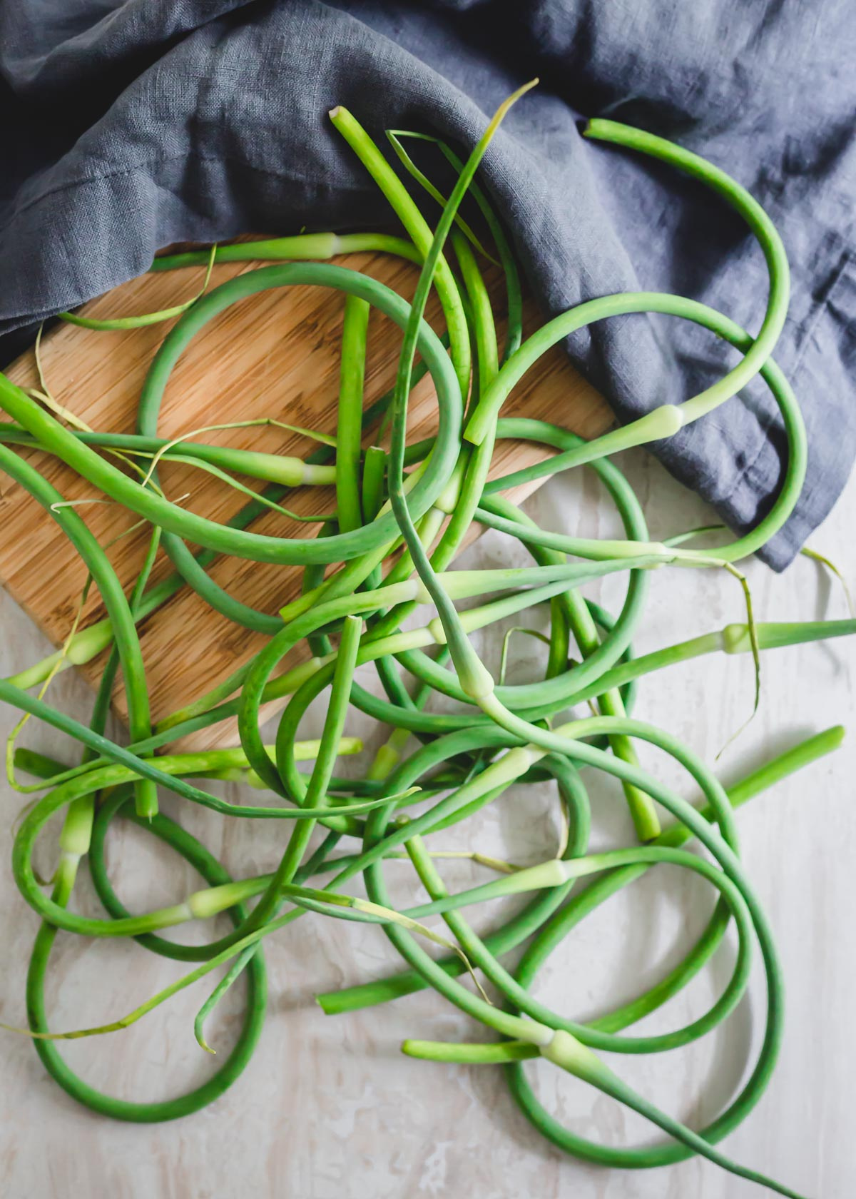 Fresh garlic scapes on a cutting board.