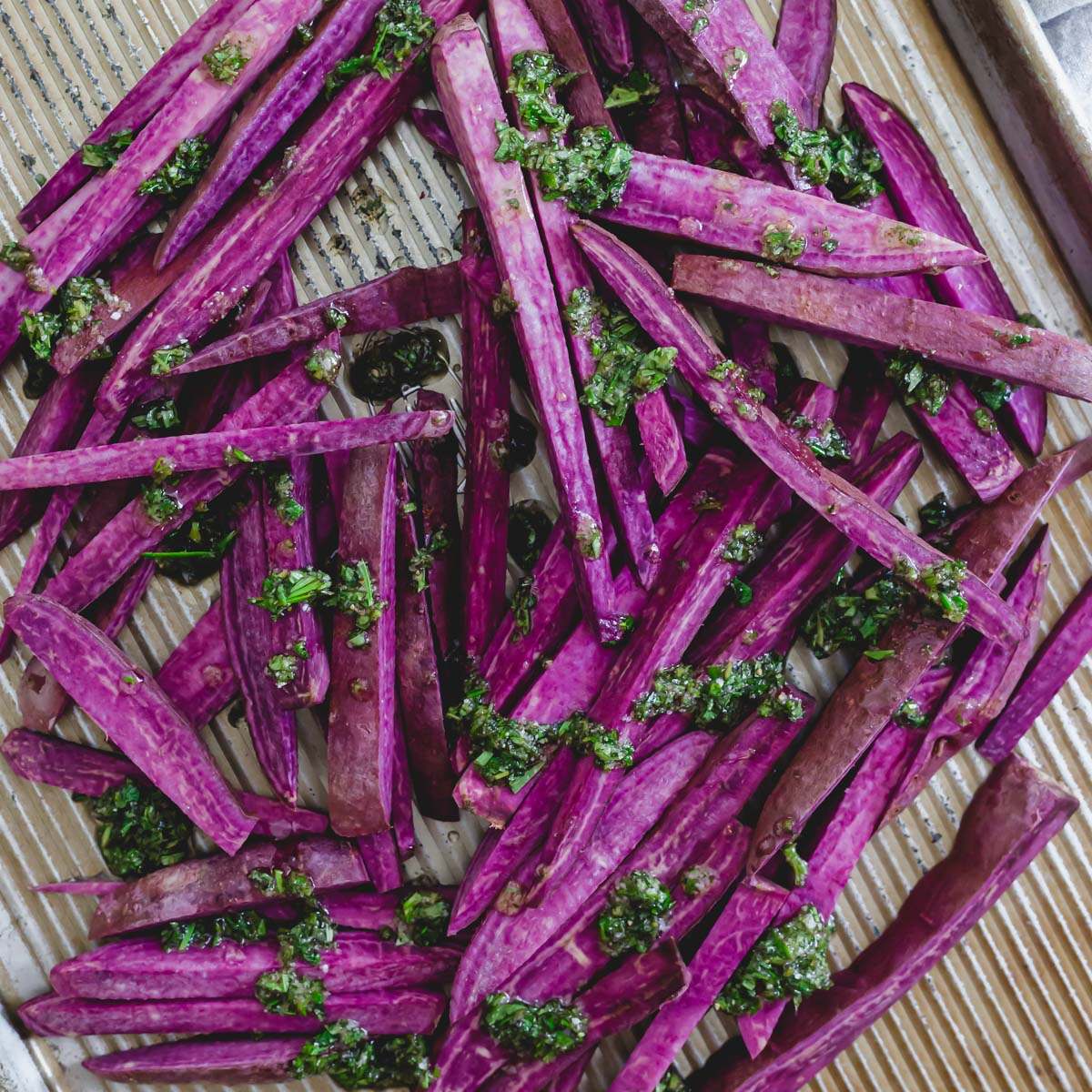 """Stokes purple sweet potatoes cut into """"fries"""" with herbs and oil before baking."""