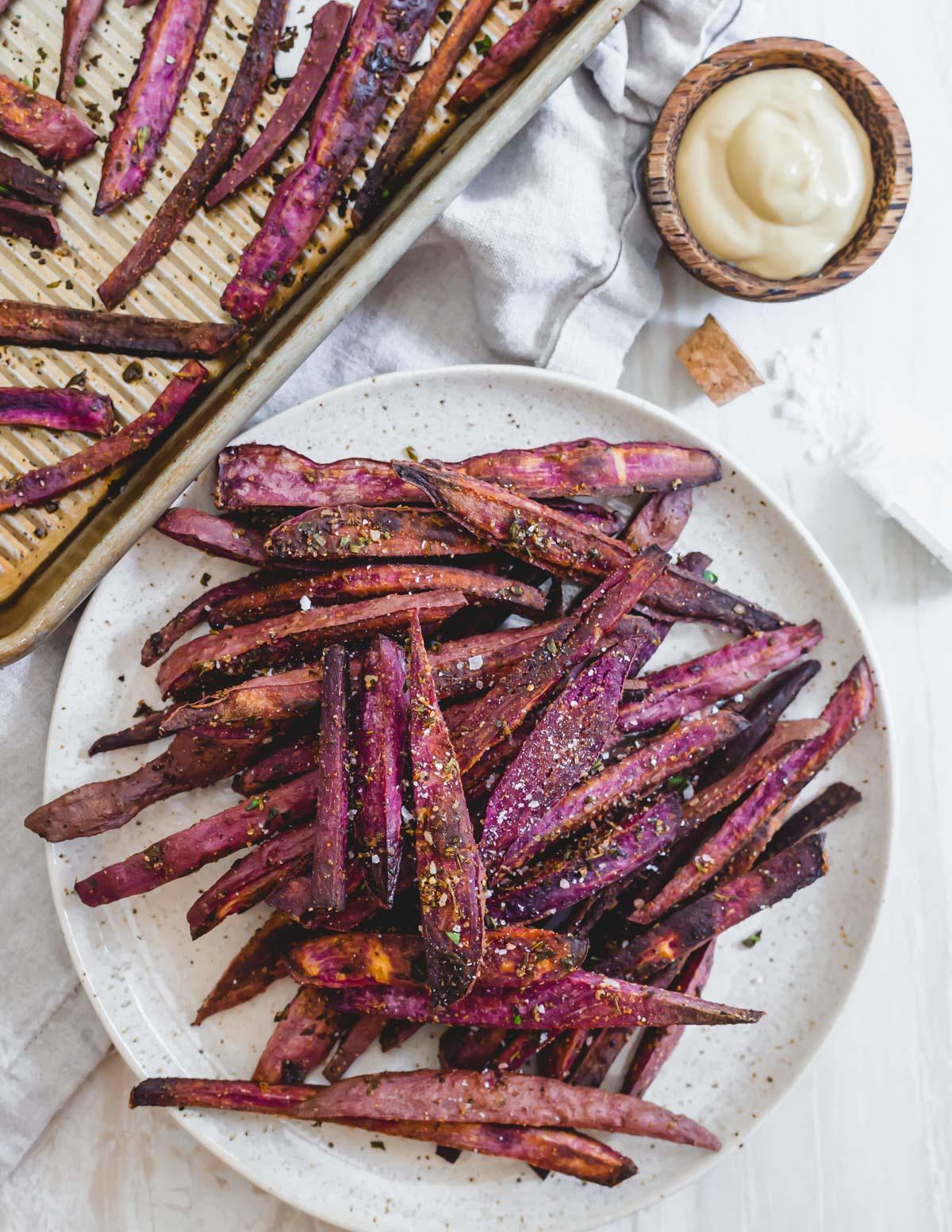 Crispy purple sweet potato fries with herbs and sea salt on a plate.
