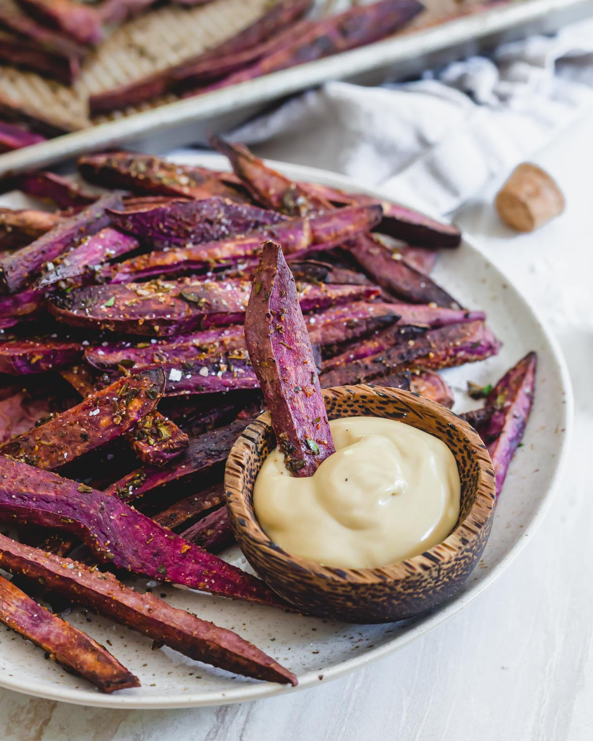 Oven baked purple sweet potato fries on a plate with mayo based dip.