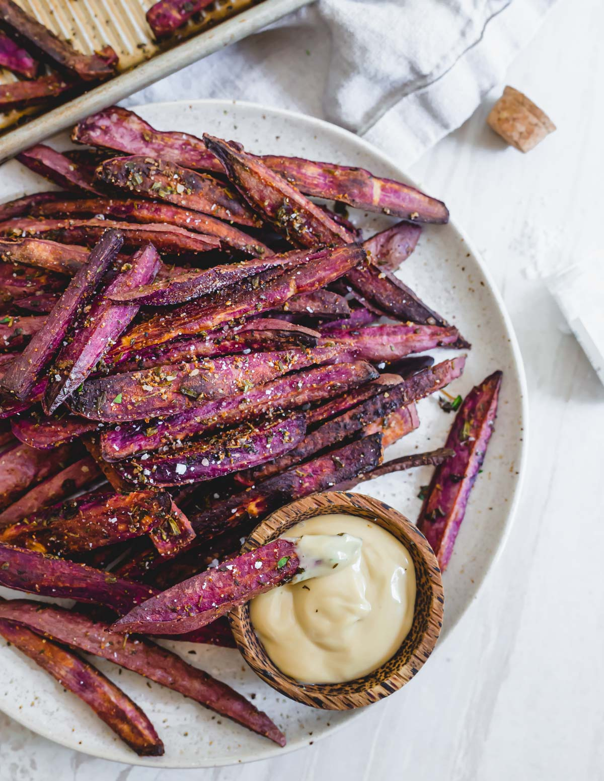 Healthy purple sweet potato fries with fresh herbs, oil and sea salt with mayo dipping sauce.