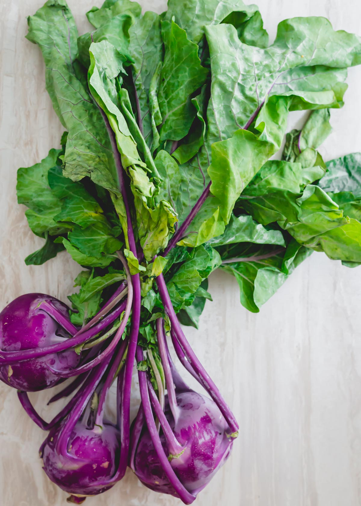 Purple kohlrabi with greens attached.