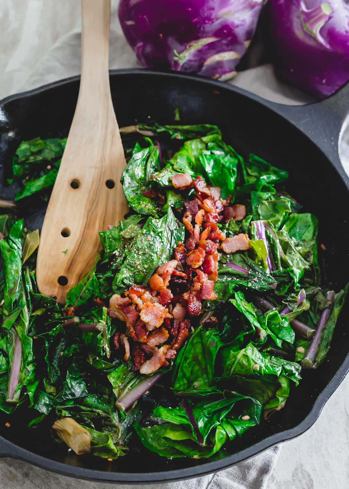 Sautéed kohlrabi greens with bacon in a cast iron skillet.