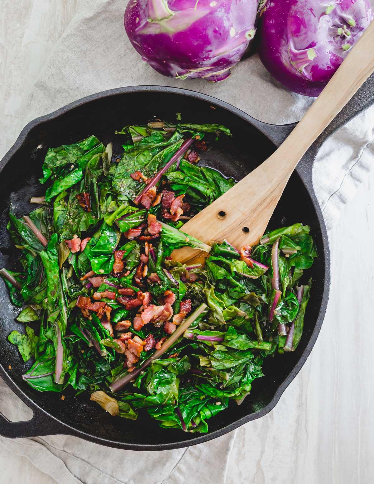 Sautéed kohlrabi greens in a skillet with crispy bacon.