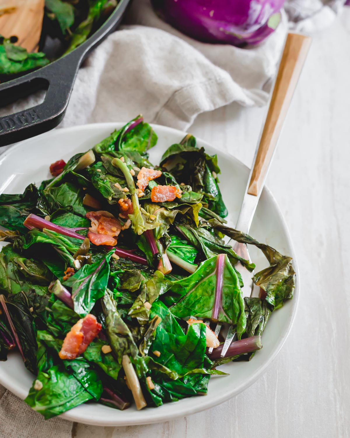 How to cook kohlrabi greens in a skillet with bacon, green onions and garlic.
