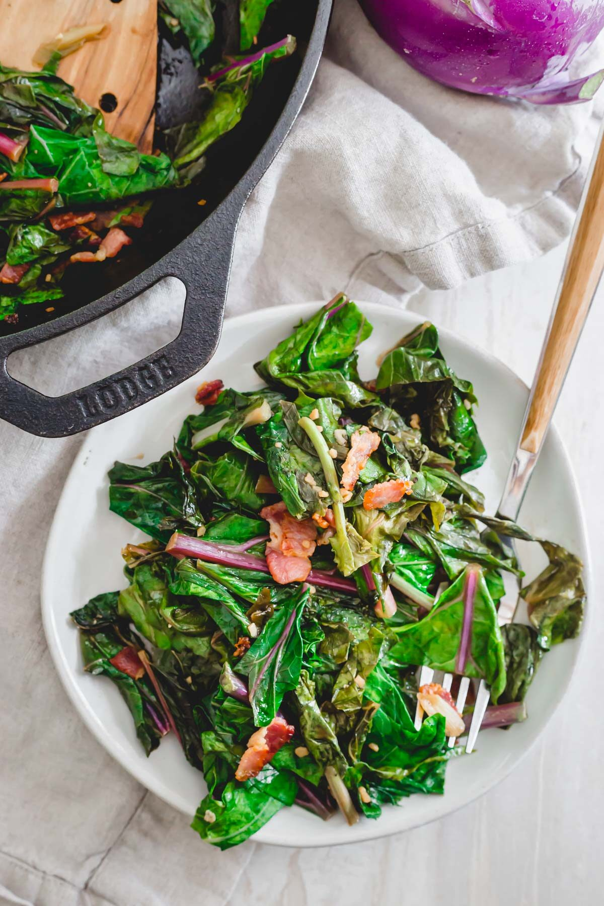 Cooked kohlrabi greens side dish with bacon, scallions and garlic.