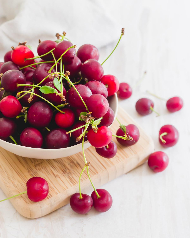 Fresh sour (tart) cherries in a bowl on a cutting board.