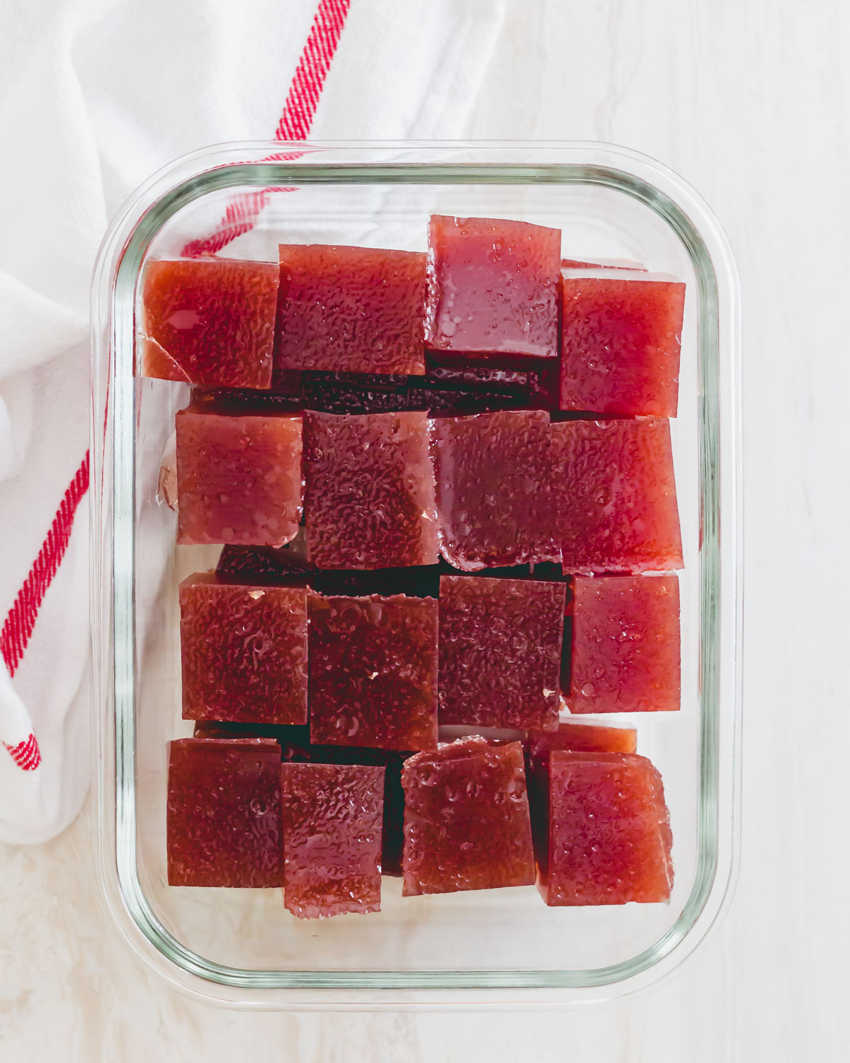 Tart cherry gummies cut into squares in a glass container for nighttime use.