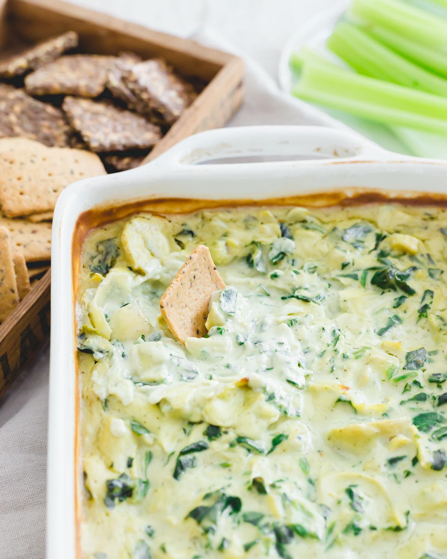 Cracker dipped in creamy vegan spinach artichoke dip.