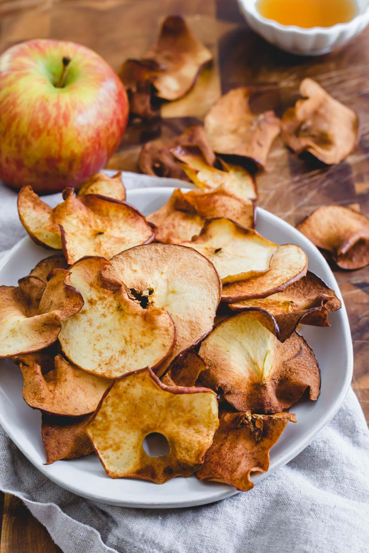 Easy maple cinnamon air fryer apple chips on a plate.