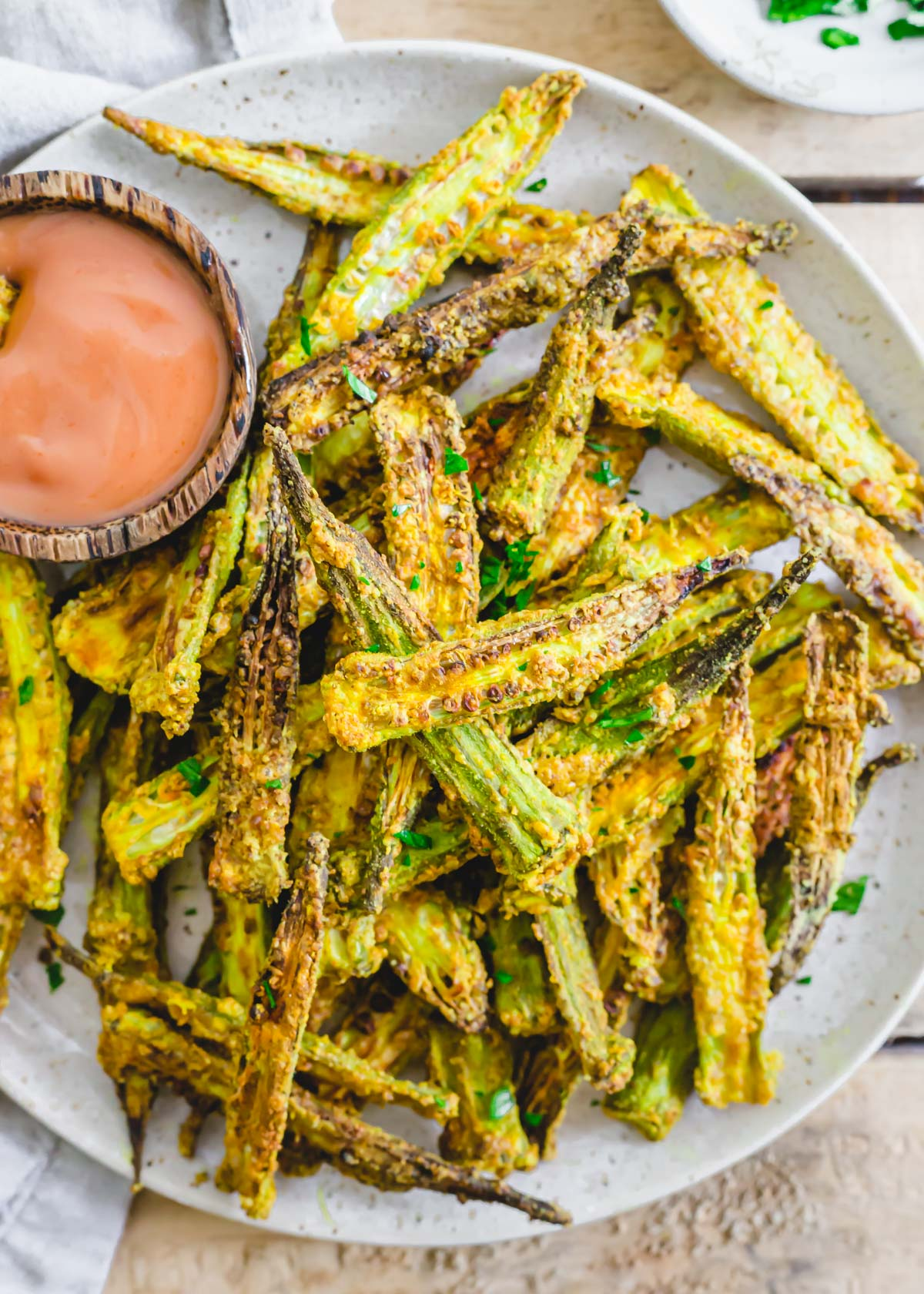 Crispy crunchy air fryer okra on a plate with dipping sauce.