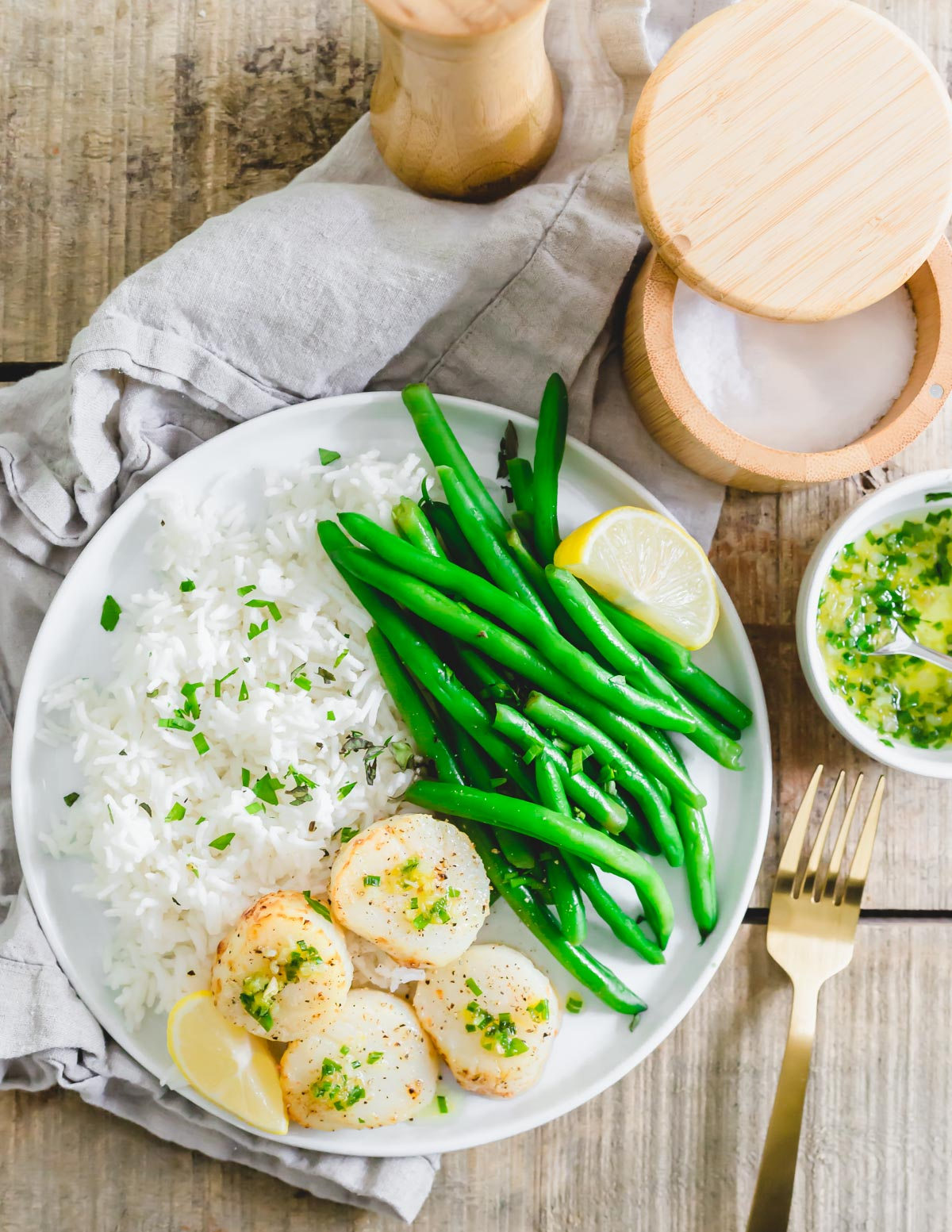 Air fryer sea scallops served with a butter chive garlic and lemon sauce, rice and green beans.