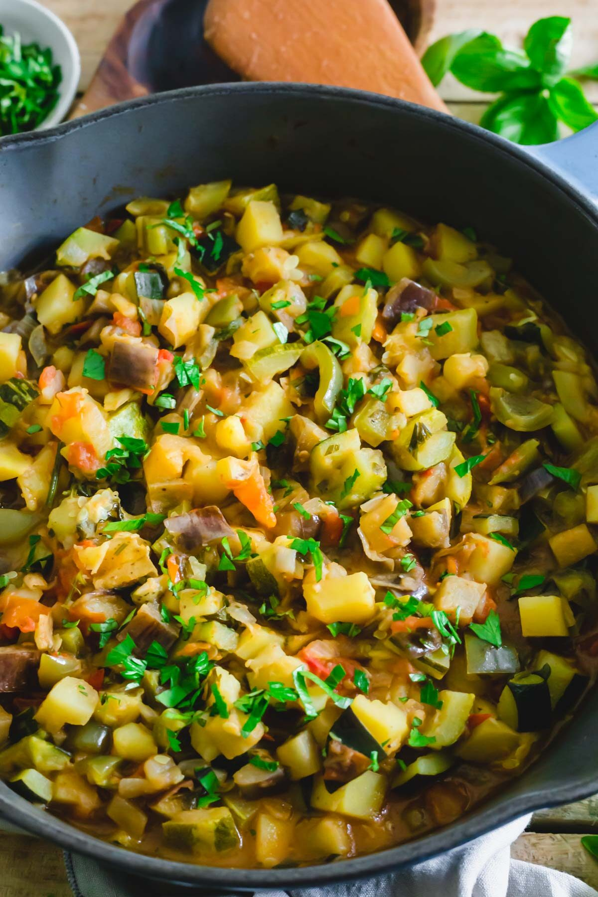 Ciambotta with eggplant, potatoes, onions, tomatoes, zucchini and peppers in a pot.