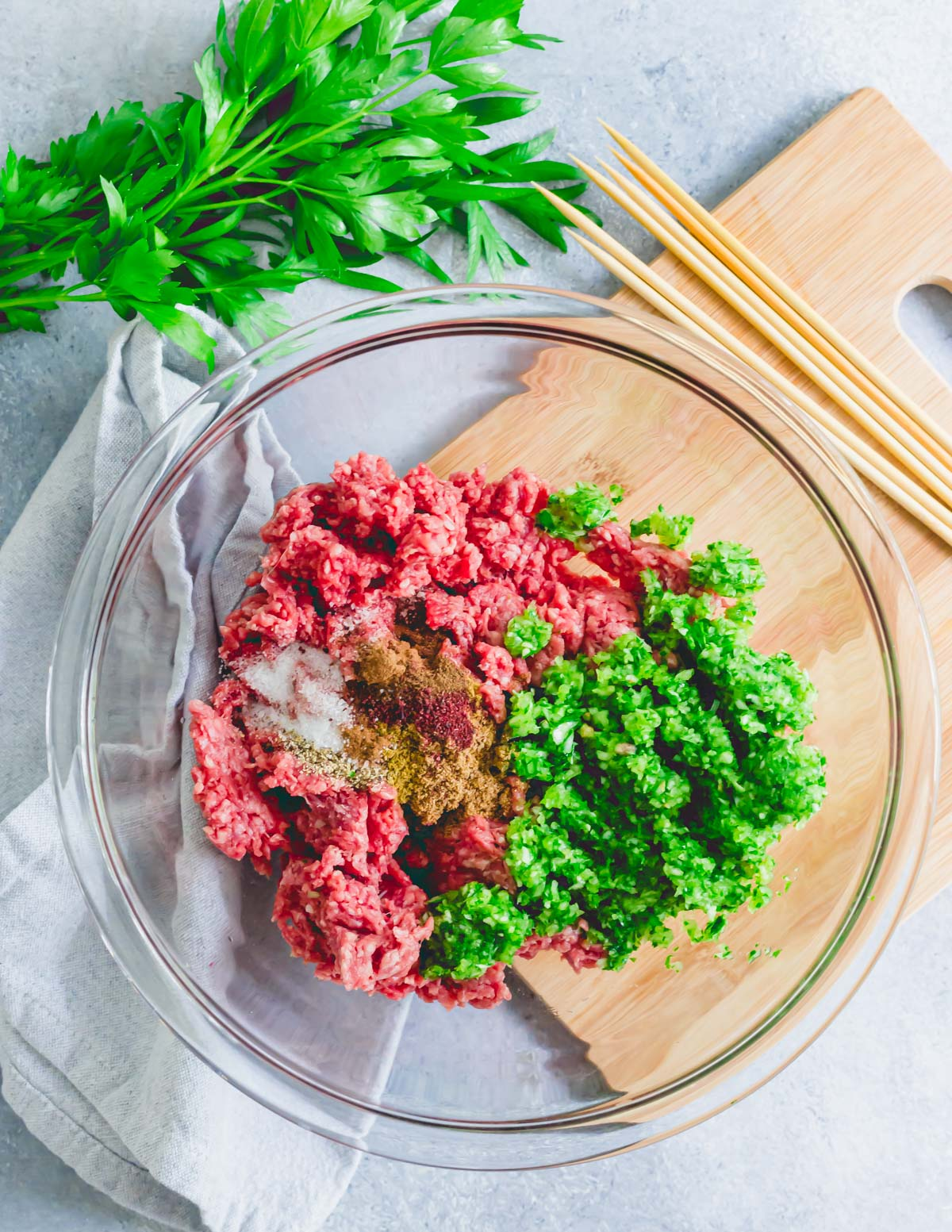 Ground beef in a mixing bowl with parsley, onion and garlic mince and spices to make beef kafta kabobs.
