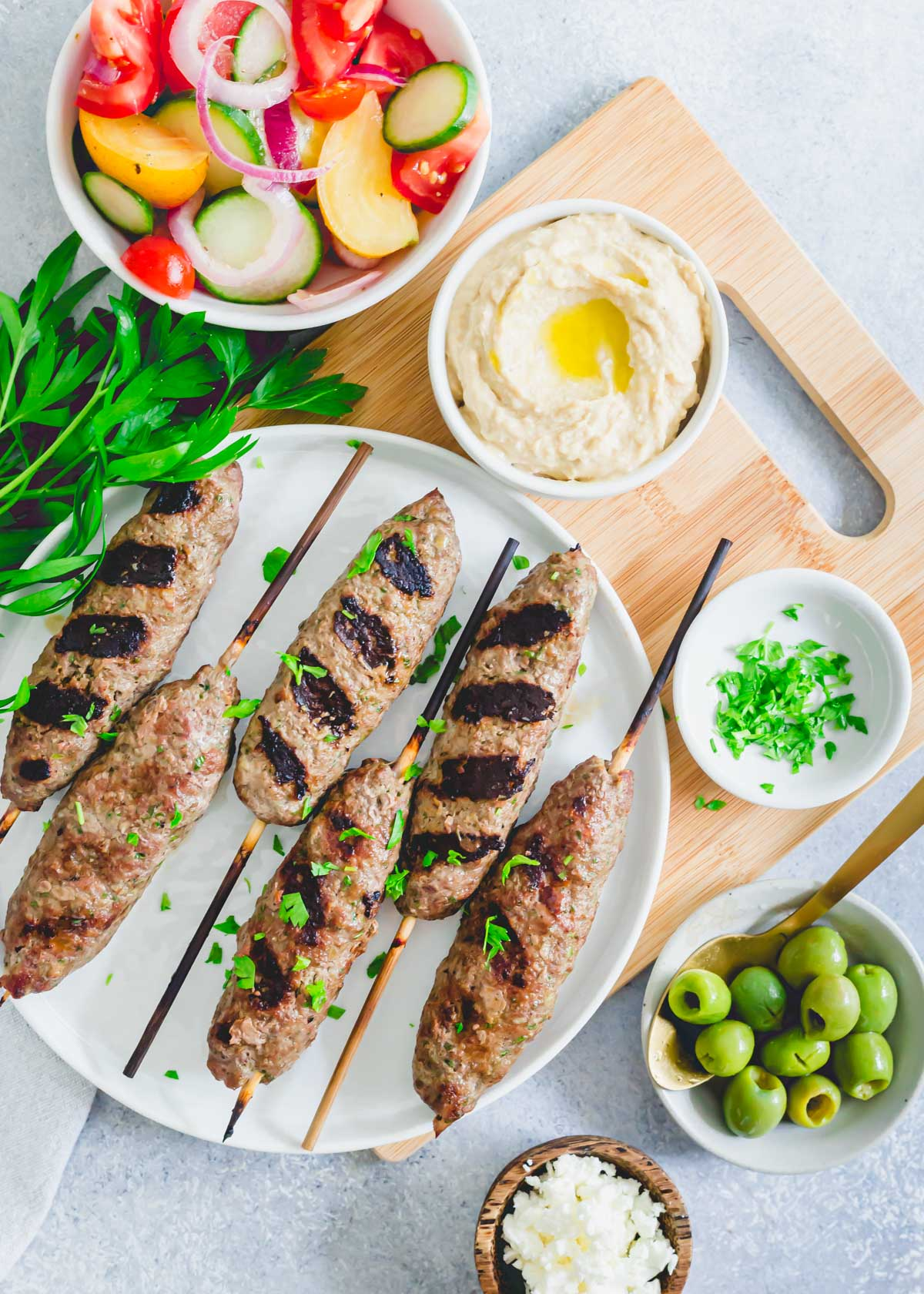 Grilled beef kafta kabobs on a plate with parsley.