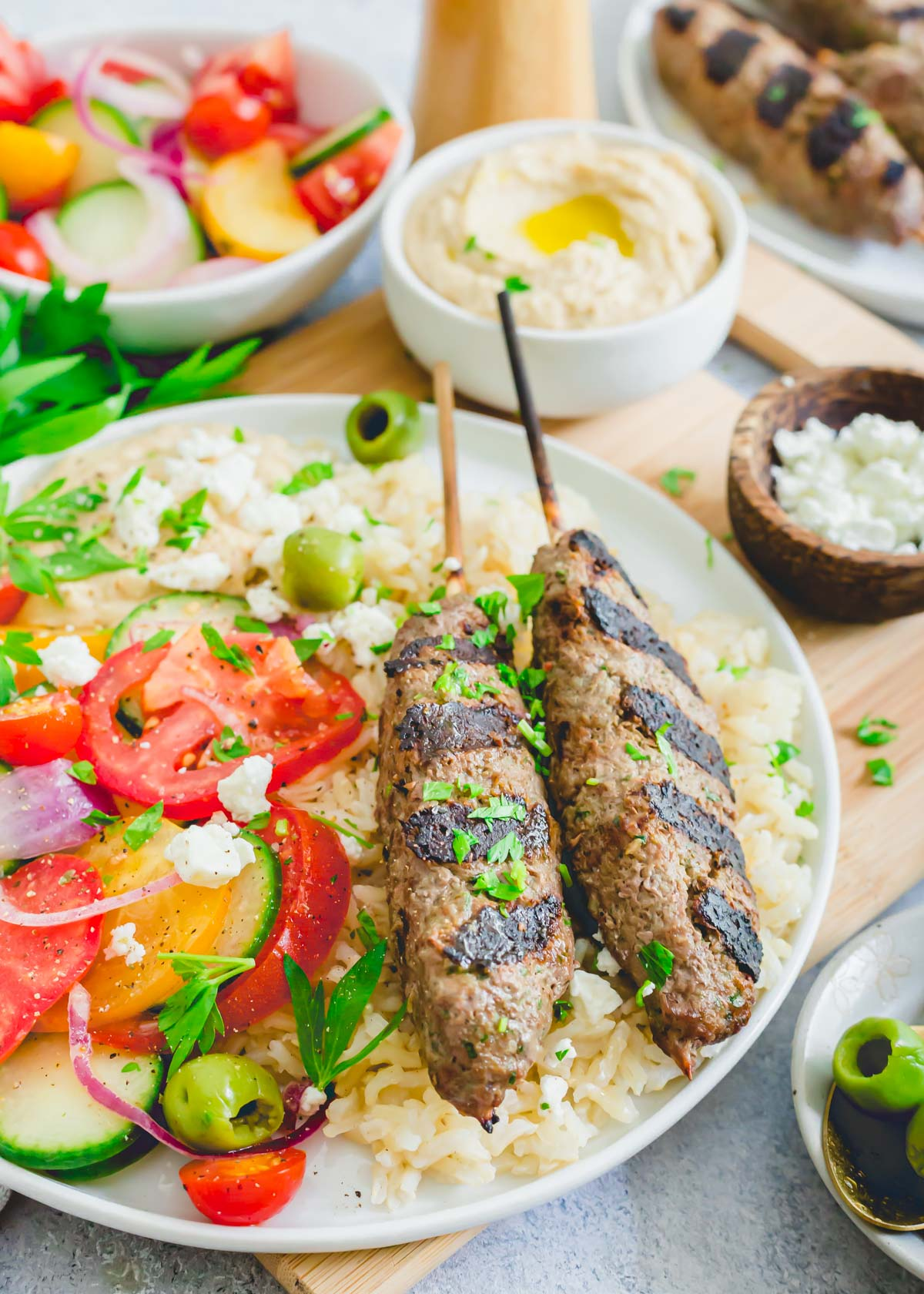 Beef kafta recipe served on kabobs with rice, tomato cucumber salad, hummus and feta.