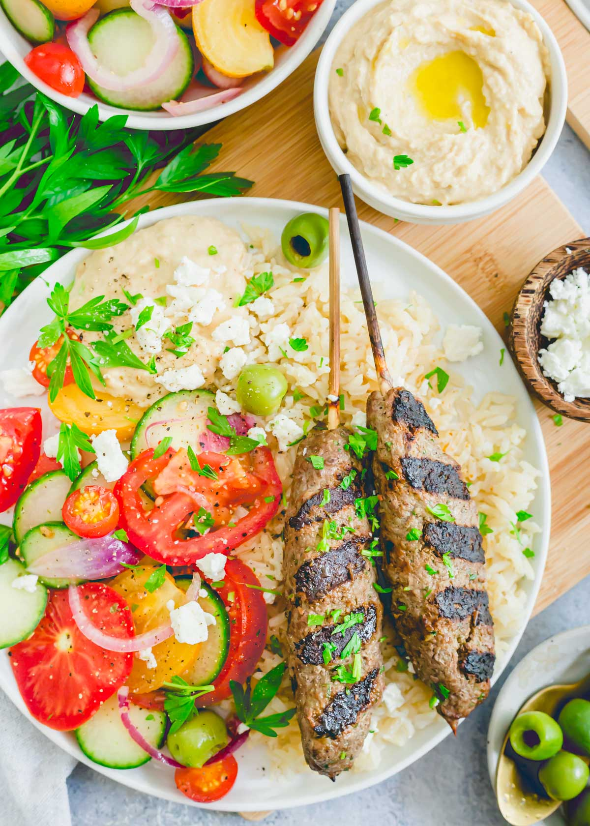 Grilled kafta kabobs made with beef on a plate with rice, tomatoes, cucumbers and red onion and hummus.
