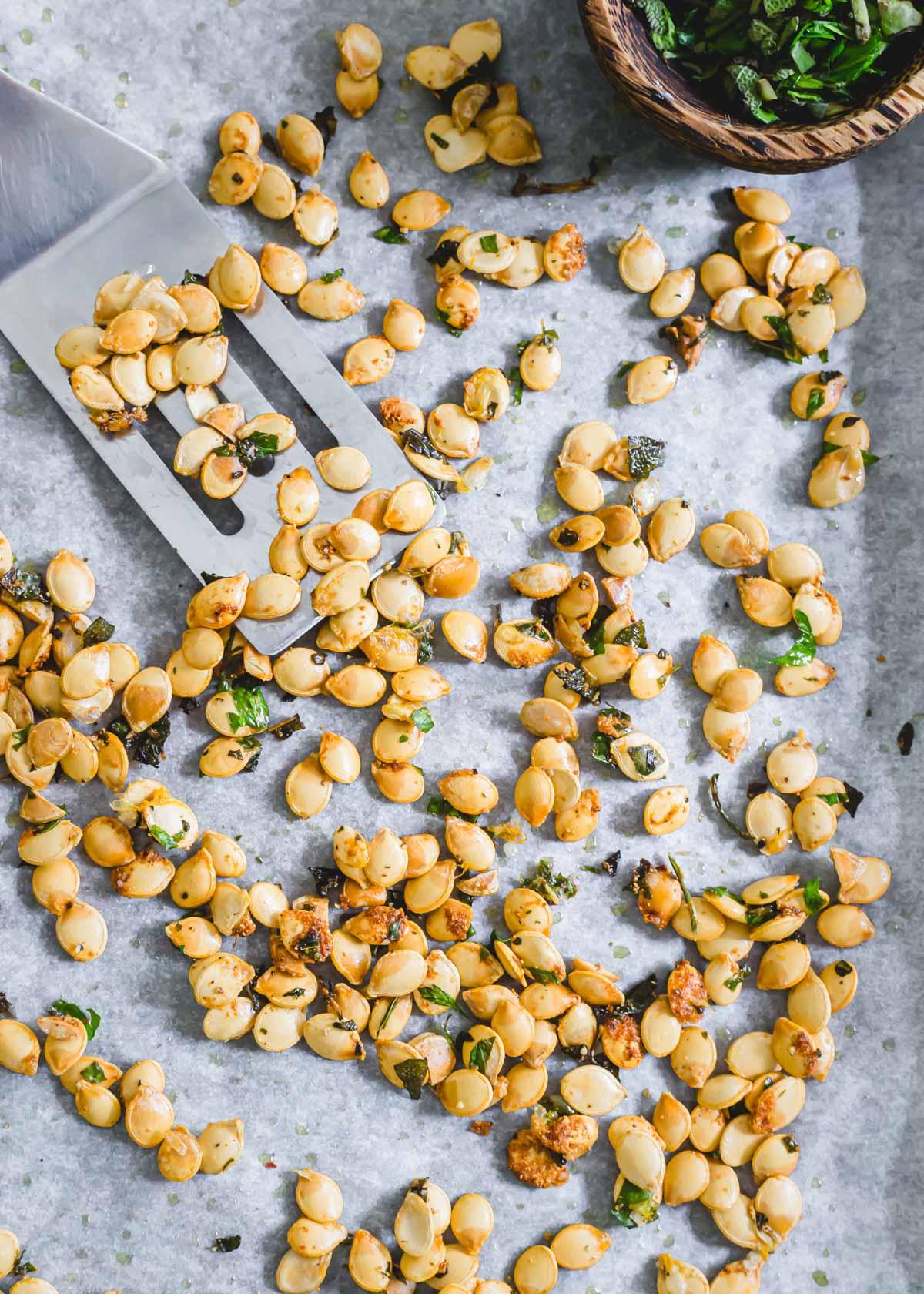 Crispy roasted delicata squash seeds on a baking sheet with spatula.