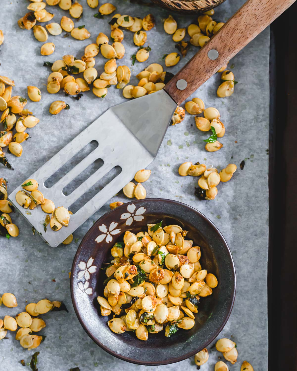 Roasted delicata squash seeds with garlic and herbs in a small bowl.