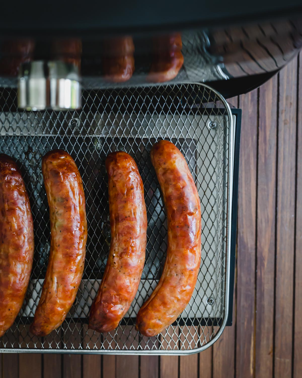 Juicy air fryer brats on the air fryer tray.