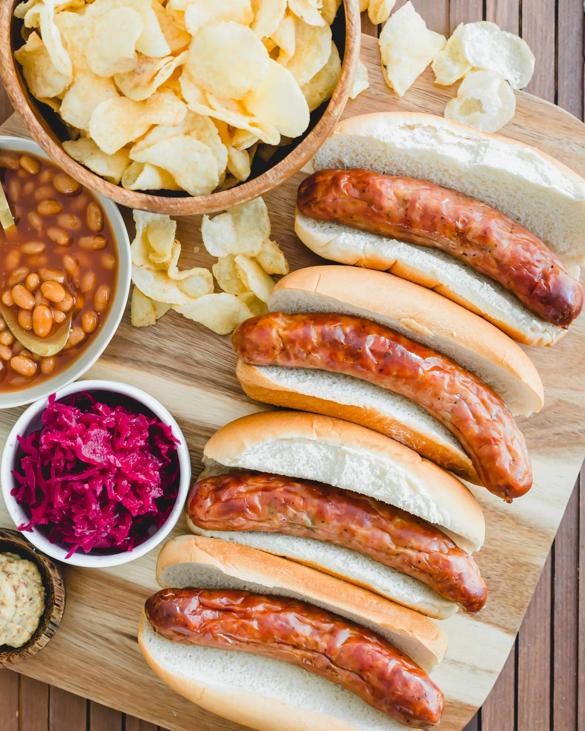 Perfectly cooked juicy bratwurst in the air fryer served with buns, potato chips, baked beans and sauerkraut.