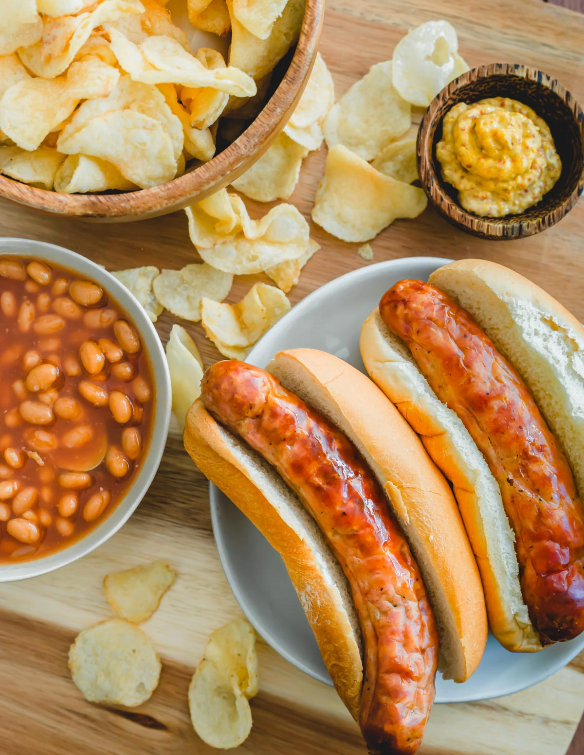 Brats cooked in the air fryer in buns with baked beans and potato chips.