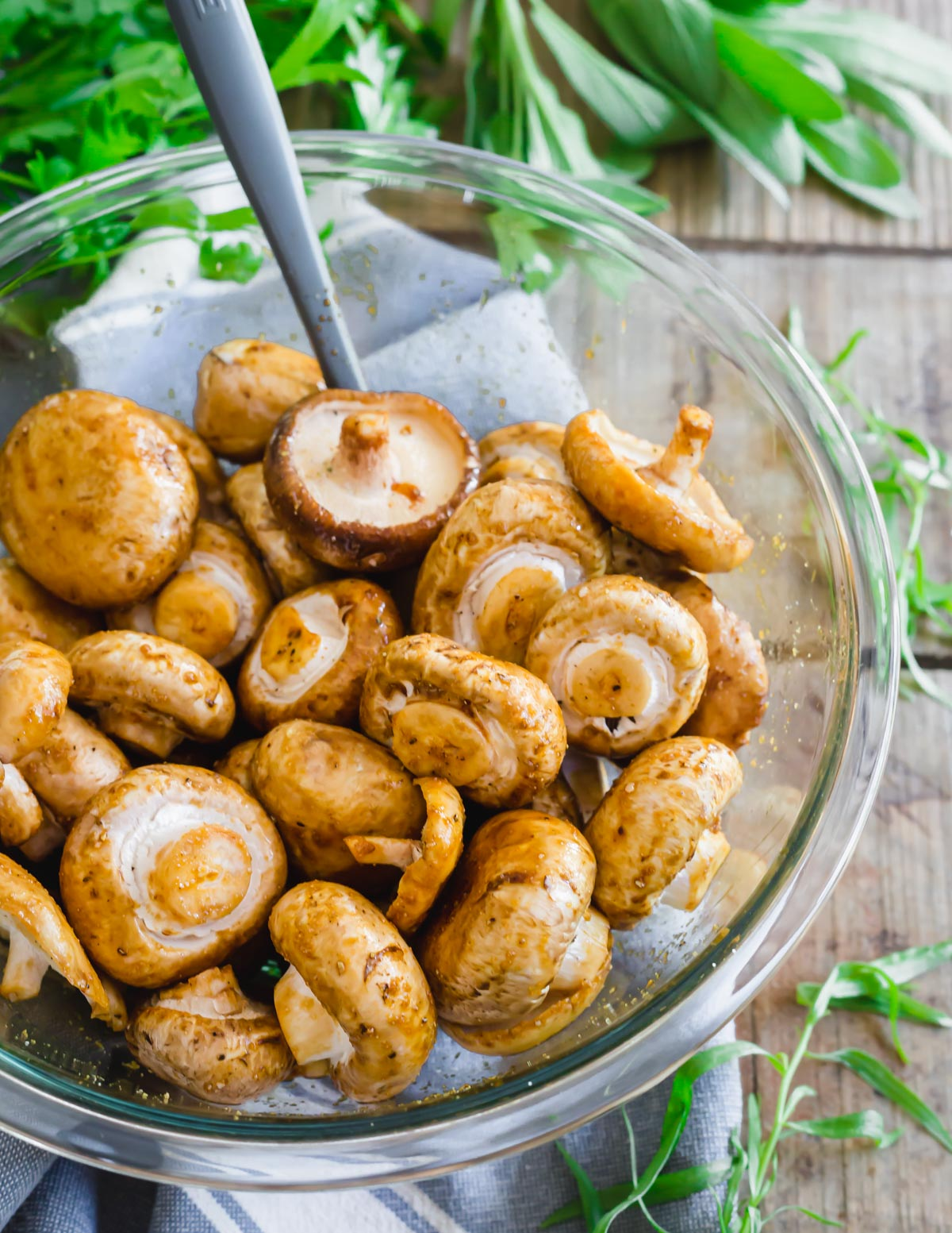 Seasoning mushrooms to be cooked in the air fryer with garlic, tamari and worcestershire sauce.